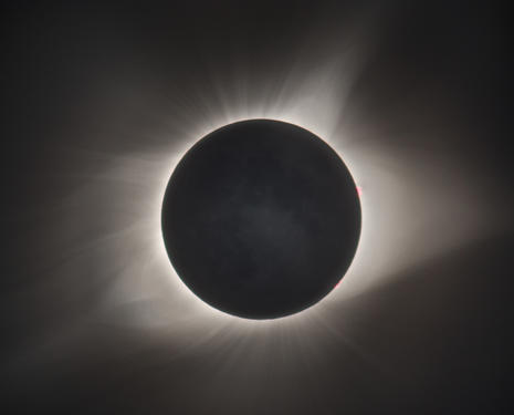 See Explanation. Clicking on the picture will download the highest resolution  version available. The Crown of the Sun Image Credit Copyright Derek Demeter  Emil Buehler Planetarium Explanation During a total solar eclipse, the Sun s  extensive outer atmosphere, or corona, is an inspirational sight. Streamers and  shimmering features visible to the eye span a brightness range of over 10,000  to 1, making them notoriously difficult to capture in a single photograph. But  this composite of telescopic images covers a wide range of exposure times to  reveal the crown of the Sun in all its glory. The aligned and stacked digital  frames were taken in clear skies above Stanley, Idaho in the Sawtooth Mountains  during the Sun s total eclipse on August 21. A pinkish solar prominence extends  just beyond the right edge of the solar disk. Even small details on the dark  night side of the New Moon can be made out, illuminated by sunlight reflected  from a Full Earth.